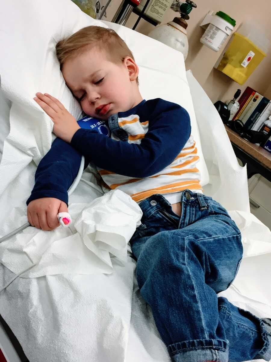 Little boy lies in a hospital bed after suffering through a febrile seizure