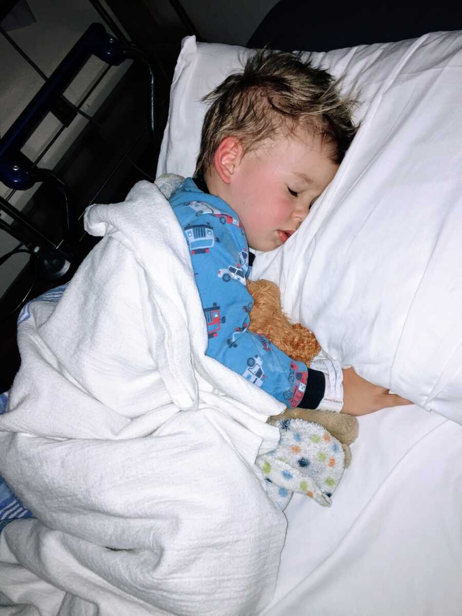 Little boy suffering from unknown seizures sleeps in a hospital bed while snuggling a stuffed animal