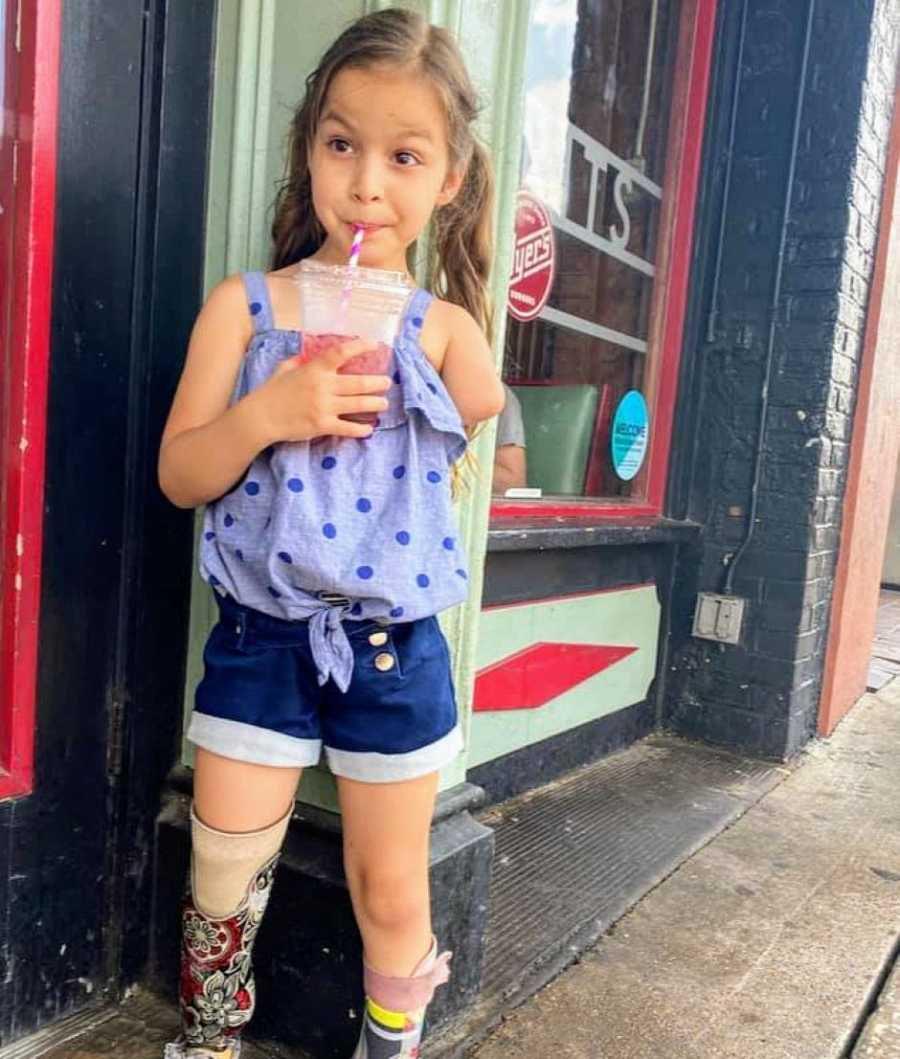 Little girl with a limb difference looks sassy while drinking a smoothie