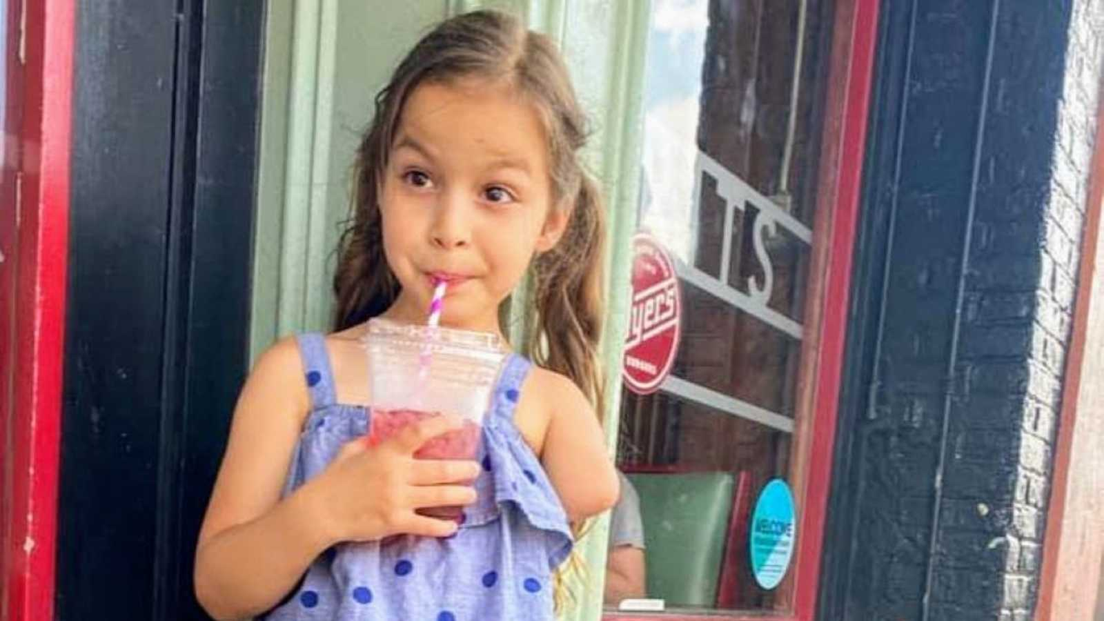 Sassy little girl with a limb difference poses with her smoothie while her mom takes a photo