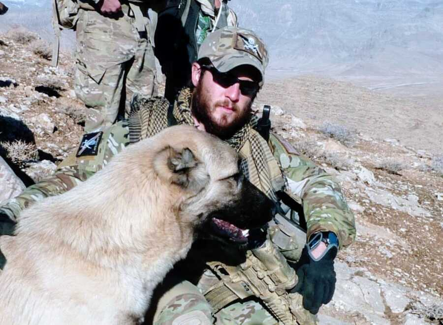 Man serving in Afghanistan takes a photo in full uniform out on a mission with a German Shepherd