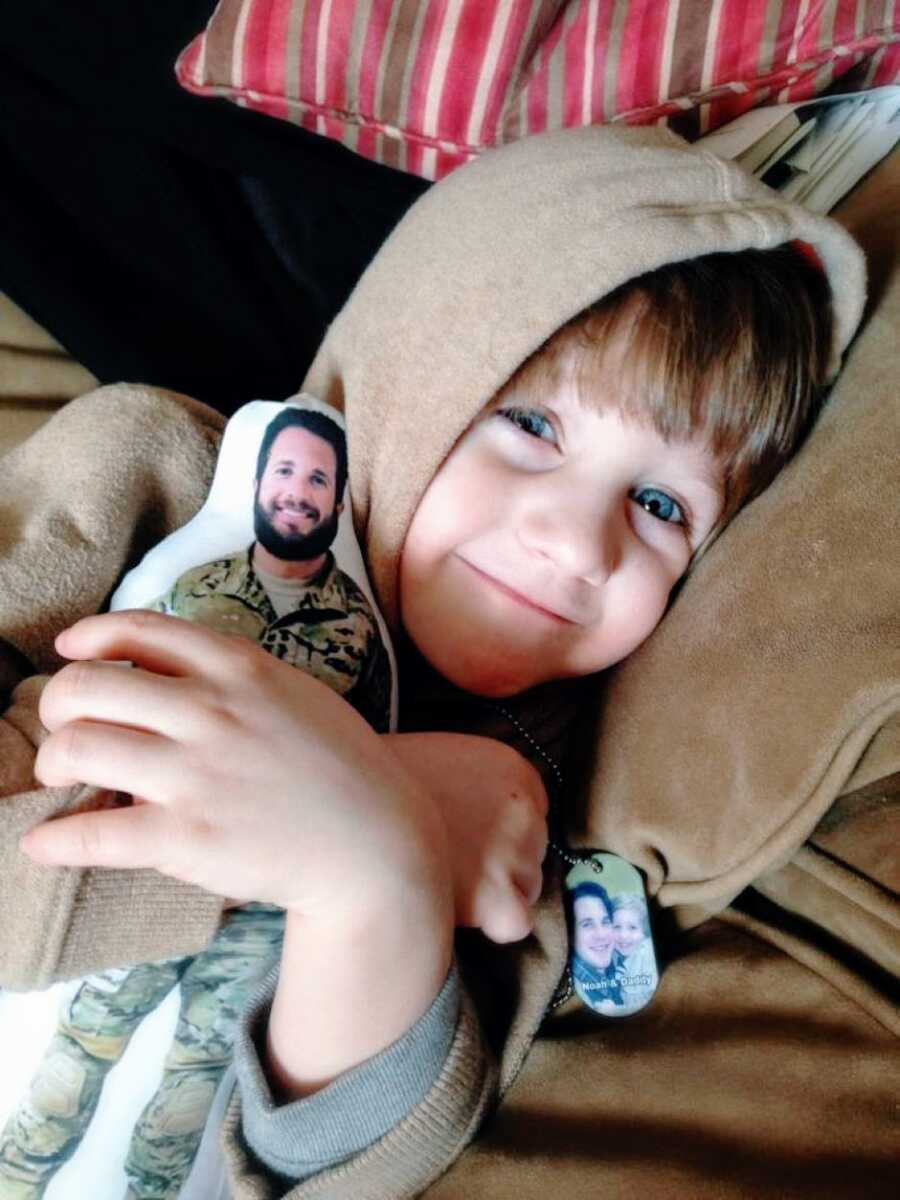Little boy cuddles with a dog tag and a doll of his dad off serving in the war in Afghanistan