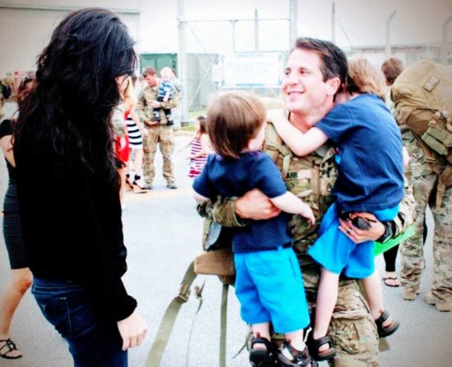 Young dad serving in the military hugs his sons and his wife after returning from Afghanistan