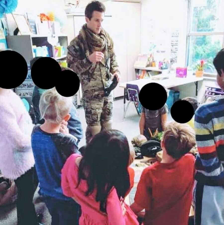 Man serving in Afghanistan stands in uniform while talking to children in a classroom