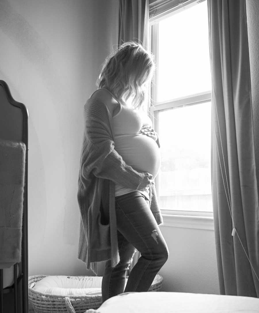 maternity photo of woman by a window