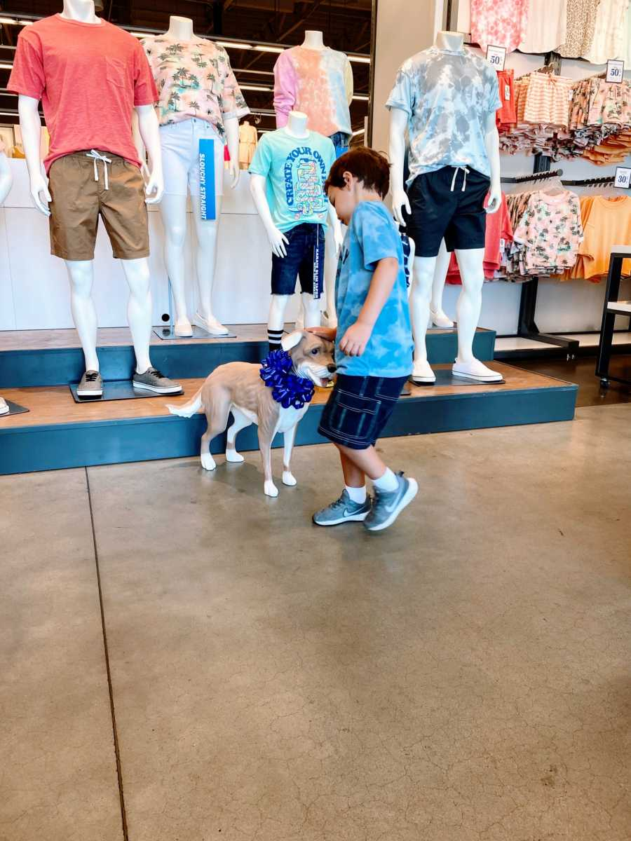 Little boy with autism pets the Old Navy Magic the mannequin dog during a shopping trip