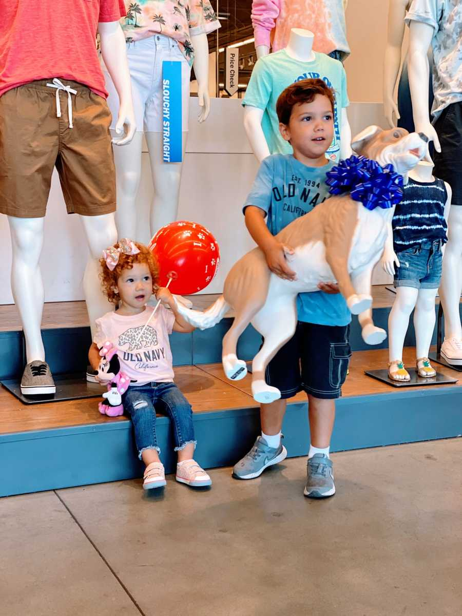 Little boy with autism holds his new Magic dog mannequin from Old Navy while his sister sits in the background holding a red balloon
