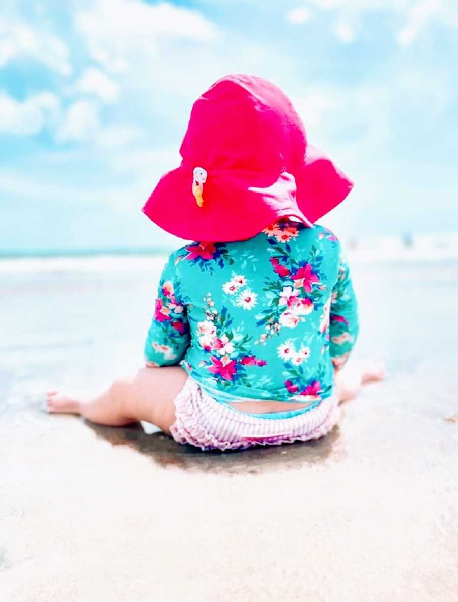 A little girl in a diaper and a sunhat looks out at the water