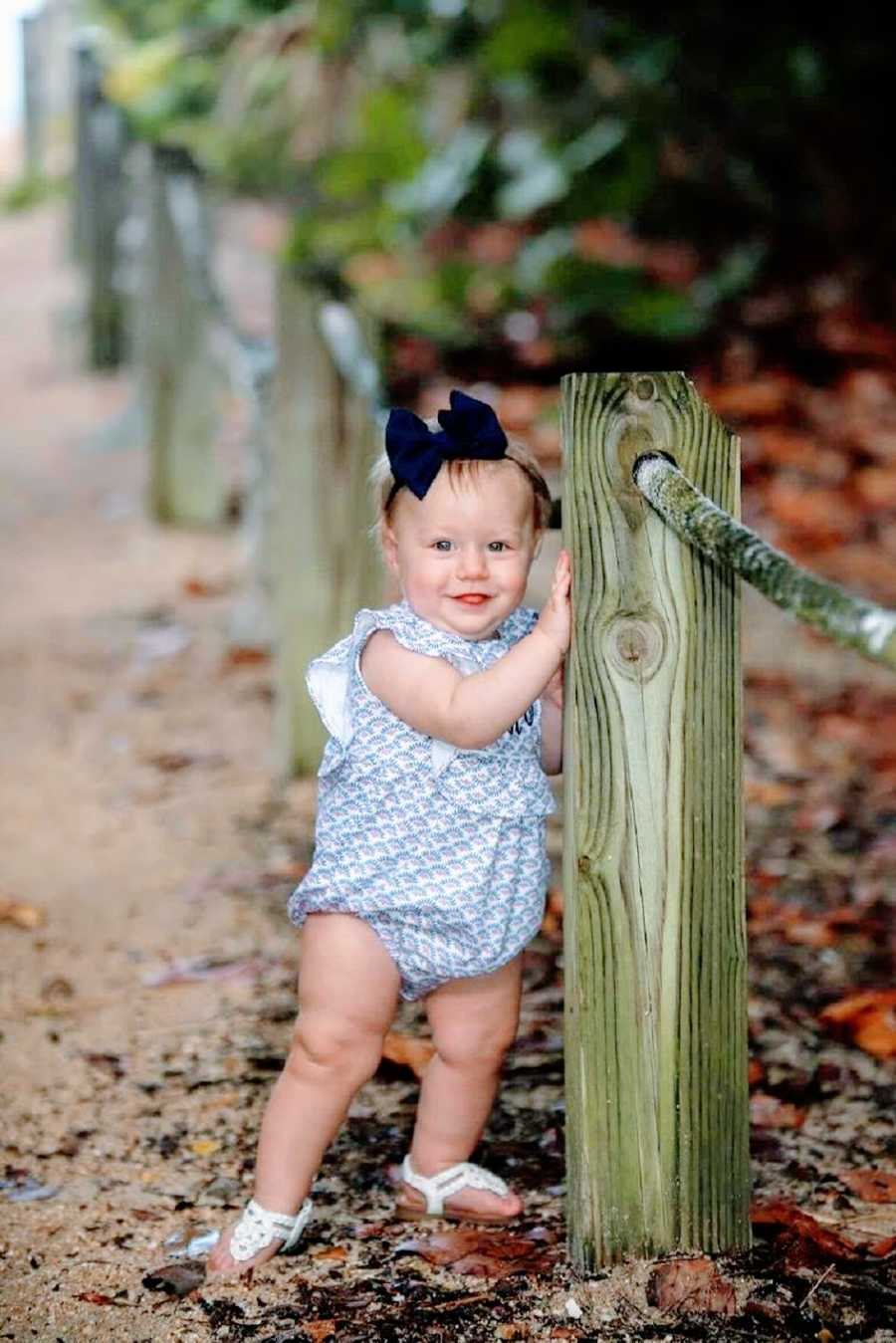 A little girl stands by a fence post