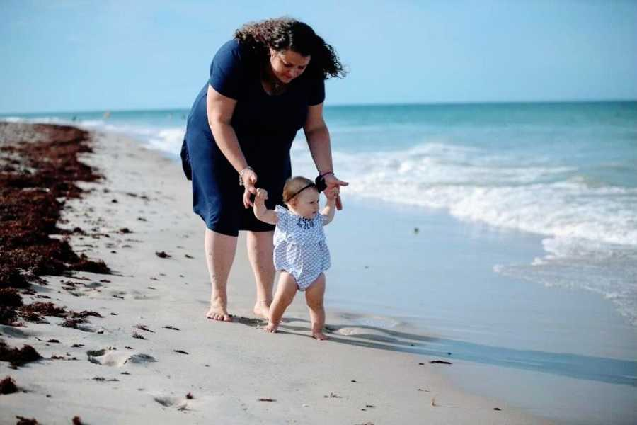 A mother helps her daughter walk along the beach