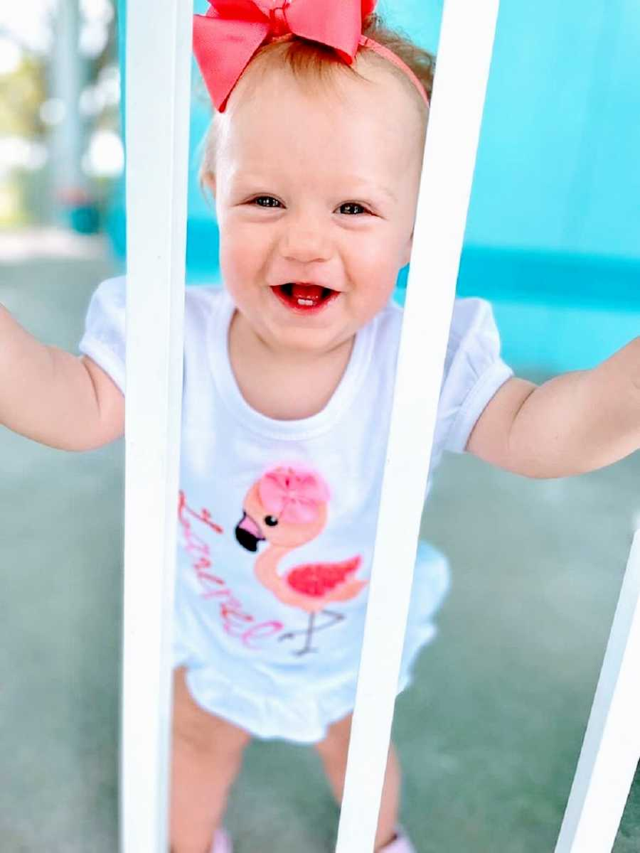 A little girl looks between bars and smiles with two teeth