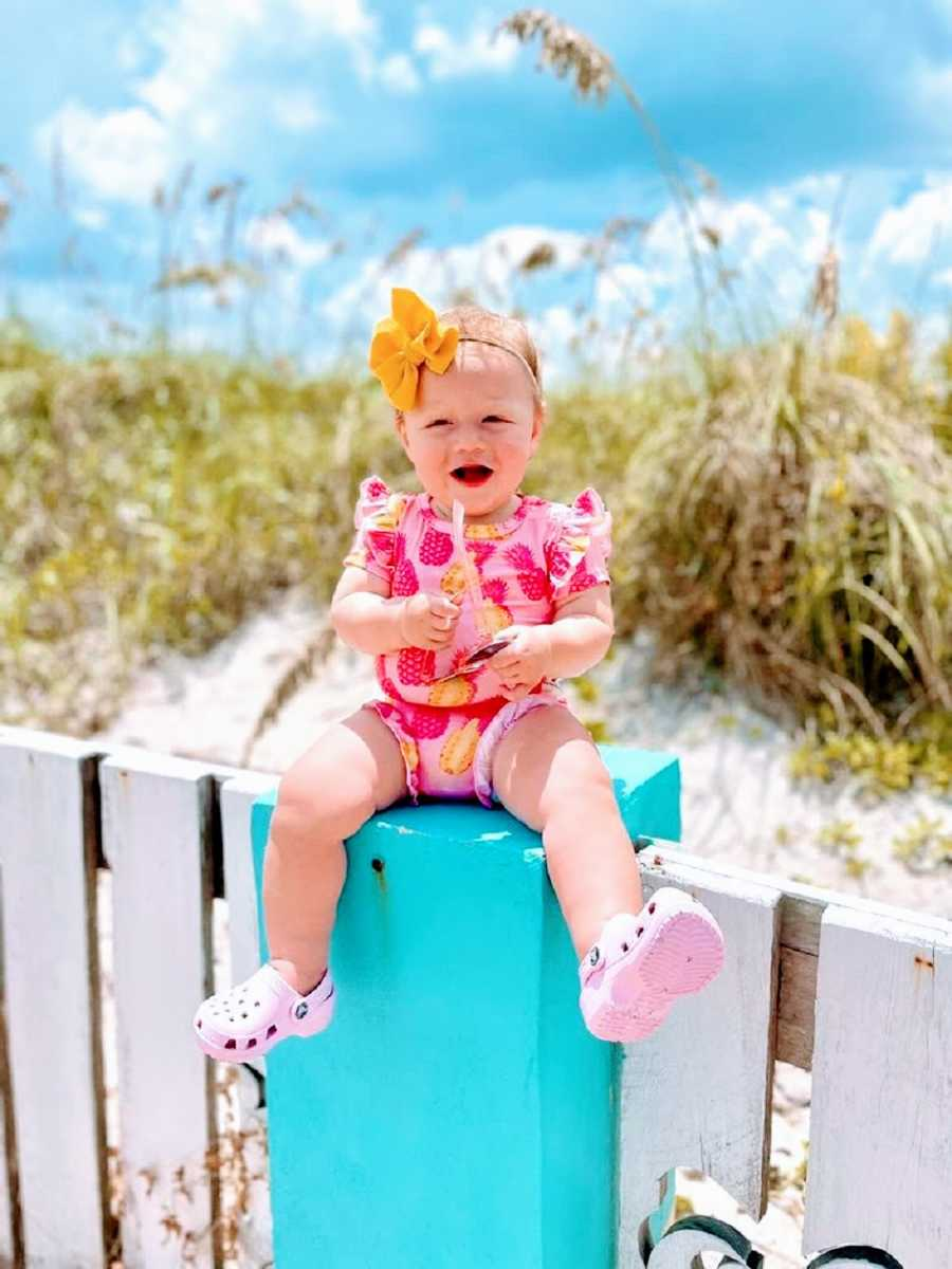 A baby girl sits on a fencepost by the sea
