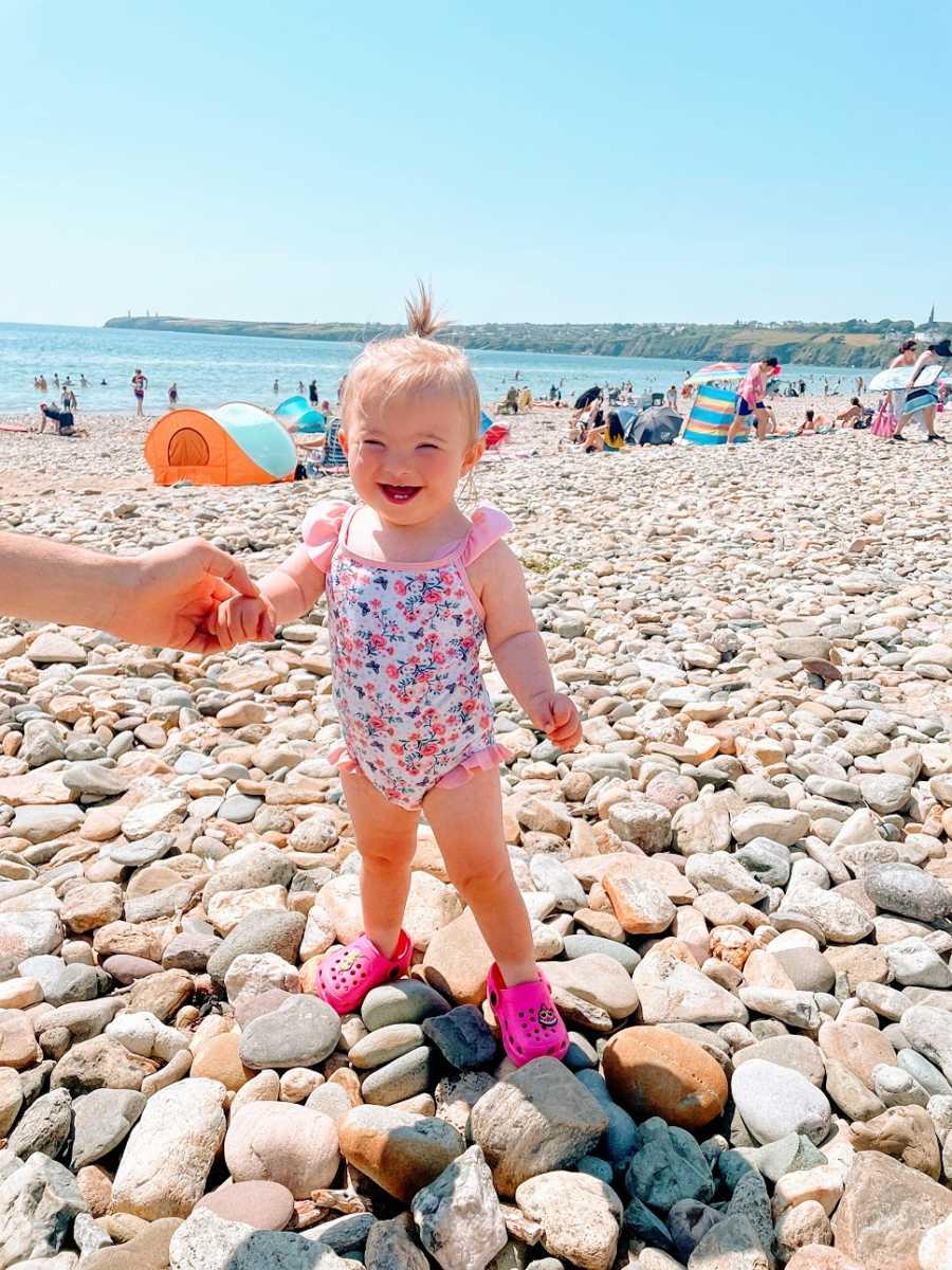 A little girl stands on a rocky beach