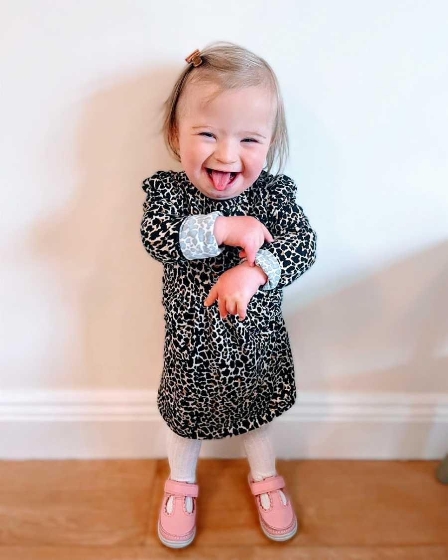 A little girl wearing a leopard-print dress makes a silly face