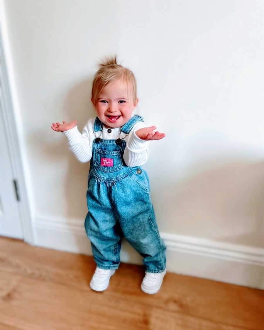 A little girl wearing overalls shrugs her shoudlers