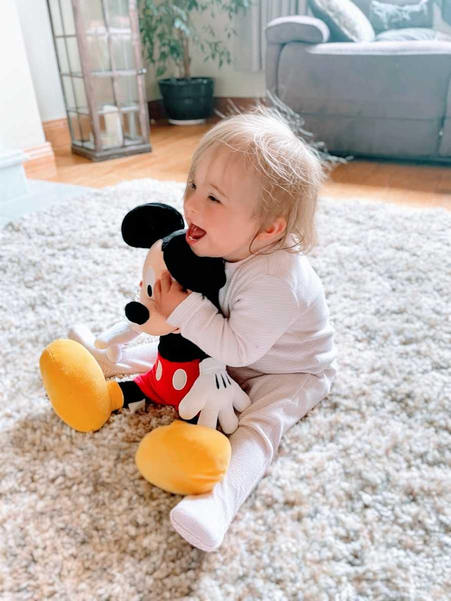 A baby girl holds a Mickey Mouse toy