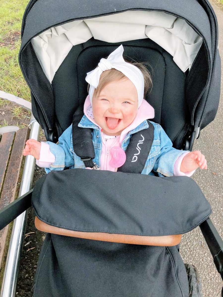 A baby girl with Down Syndrome sits in a stroller