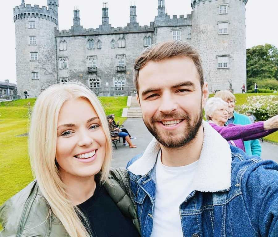 A woman and her partner stand outside an old castle