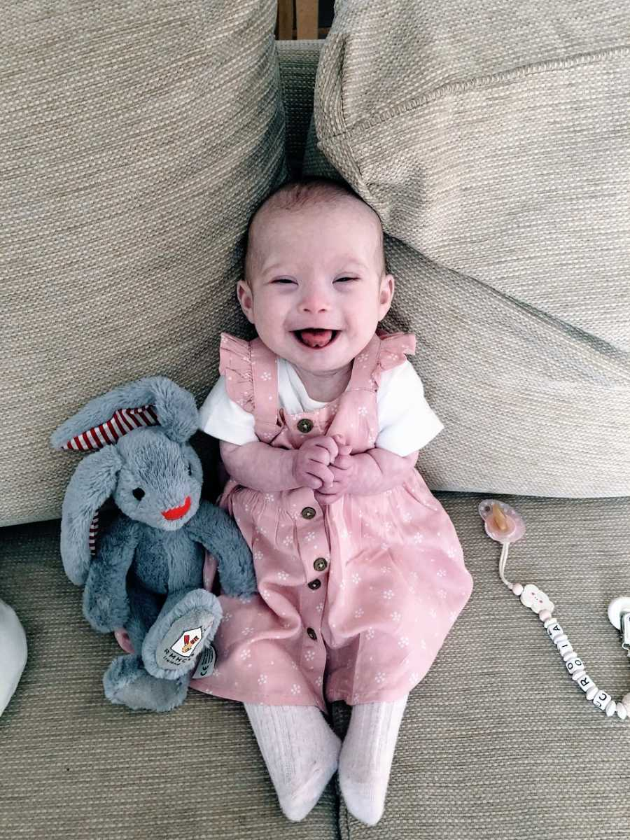 A little girl with Down Syndrome sits on a couch with a toy rabbit