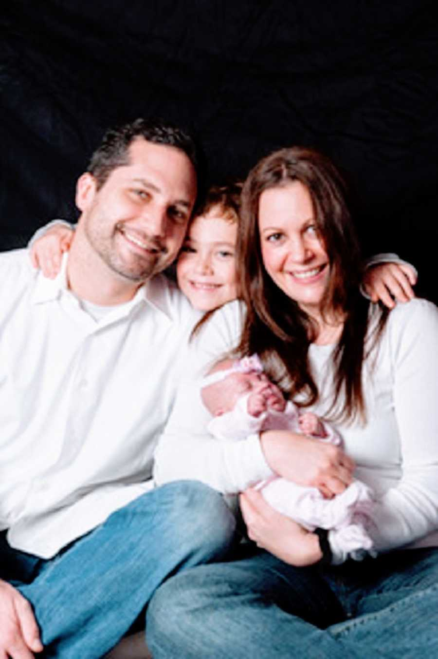 A family of four with their newborn baby girl