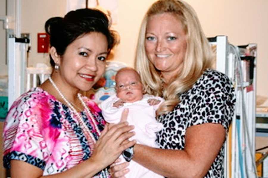 A pair of NICU nurses hold up a tiny baby girl