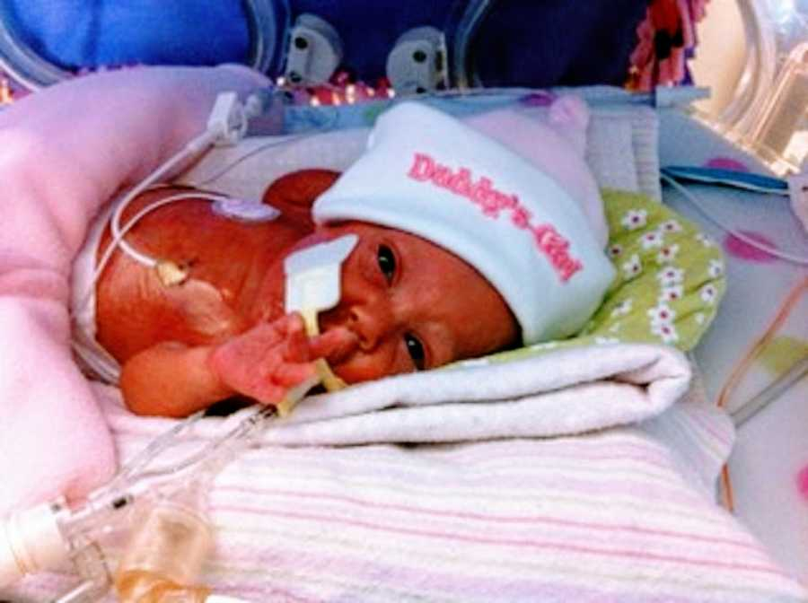 A baby girl wearing a pink hat lies in the NICU