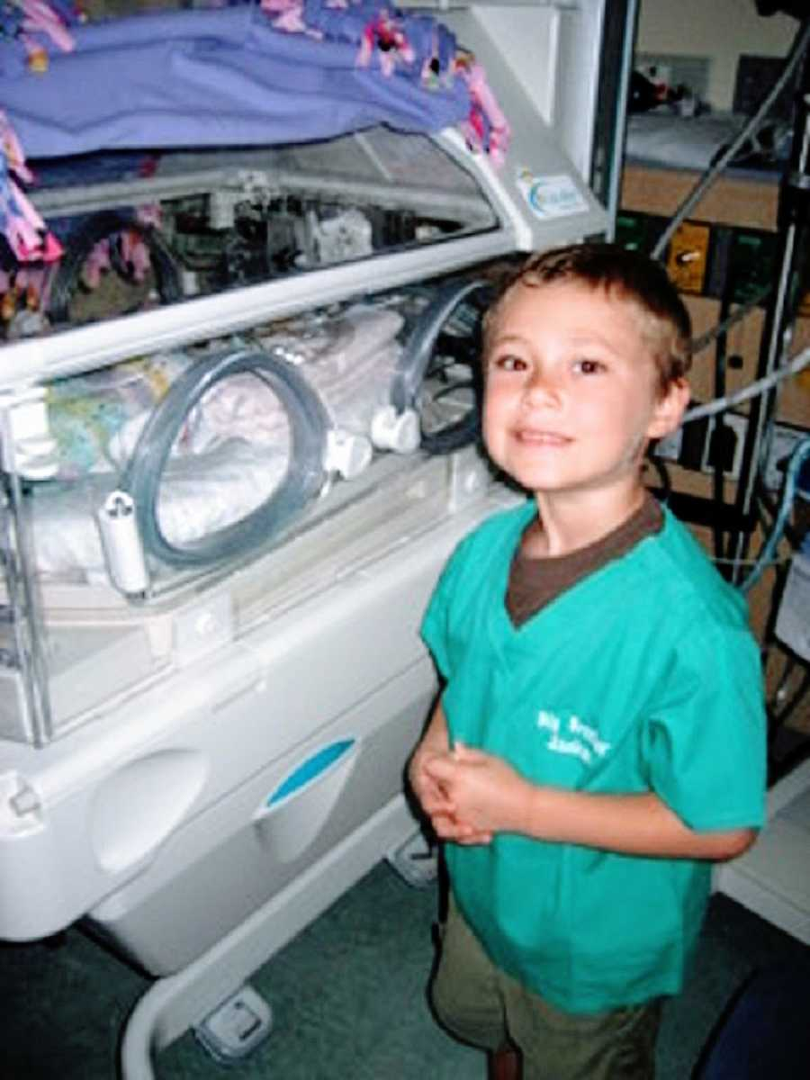 A little boy stands in the NICU visiting his baby sister