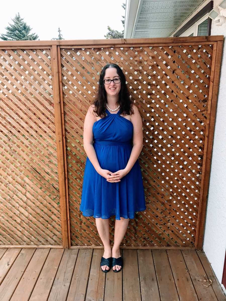 Woman wearing blue dress stands by fence