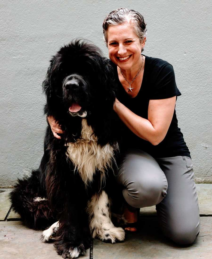 A woman sits with her big black Newfoundland