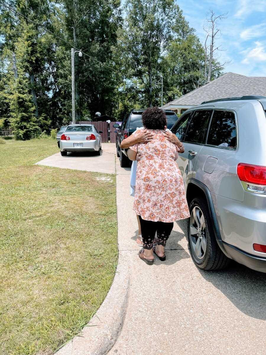 Adoptee hugs long lost biological sibling in driveway