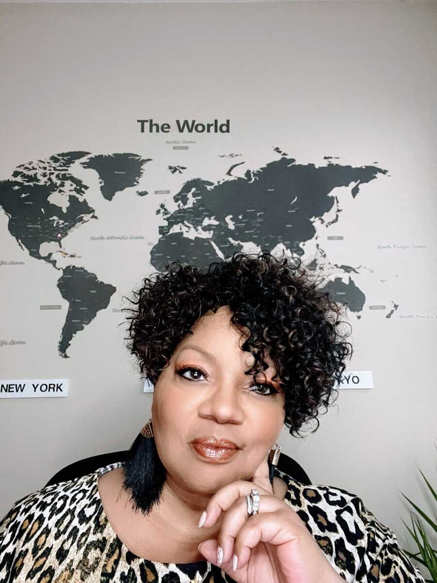 Adoptee sitting in front of map of the world