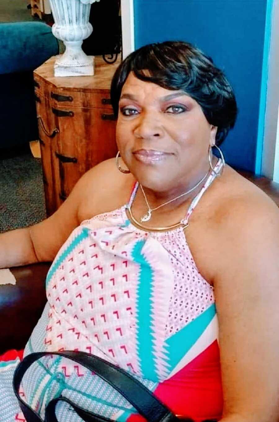 Woman seated wearing pink tank top