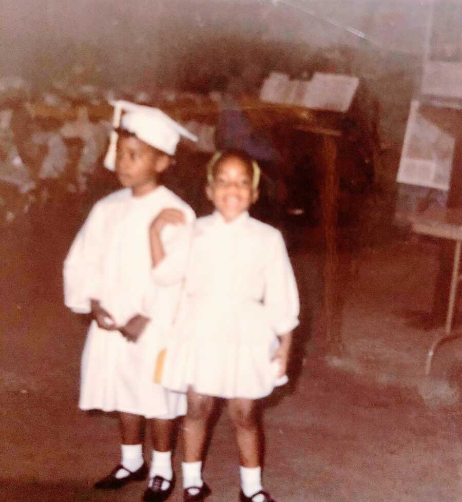 Two little girls dressed in caps and gowns for graduation