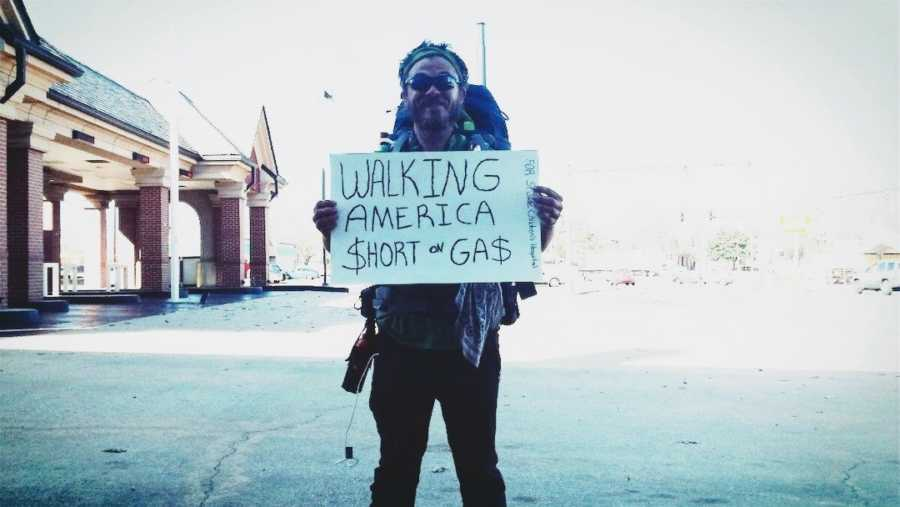 homeless man holding up a sign