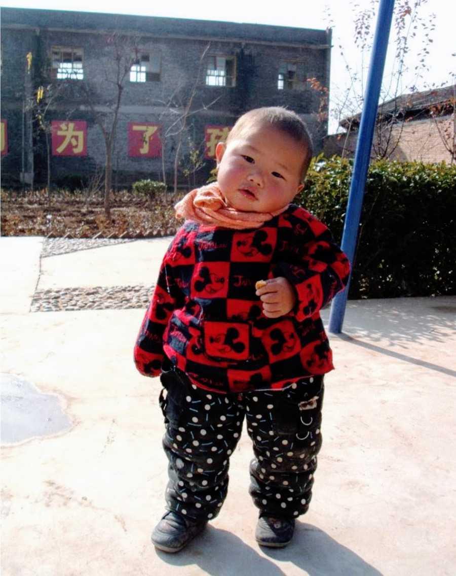 Little boy outside dressed in red coat