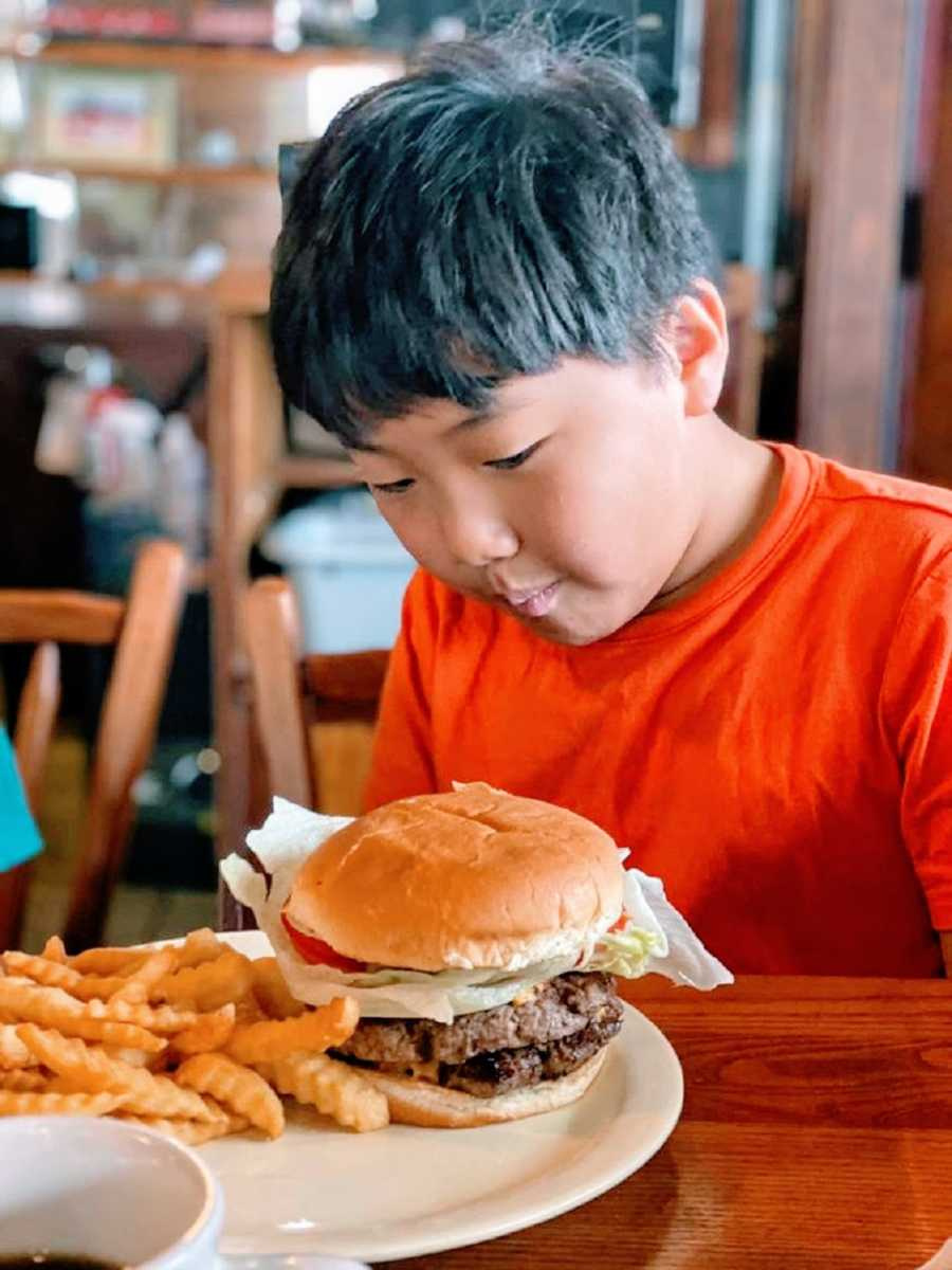 Boy in red shirt looks at hamburger on plate