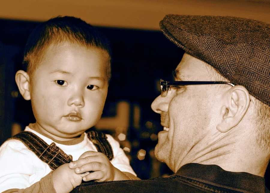 Father holds adoptive son from China
