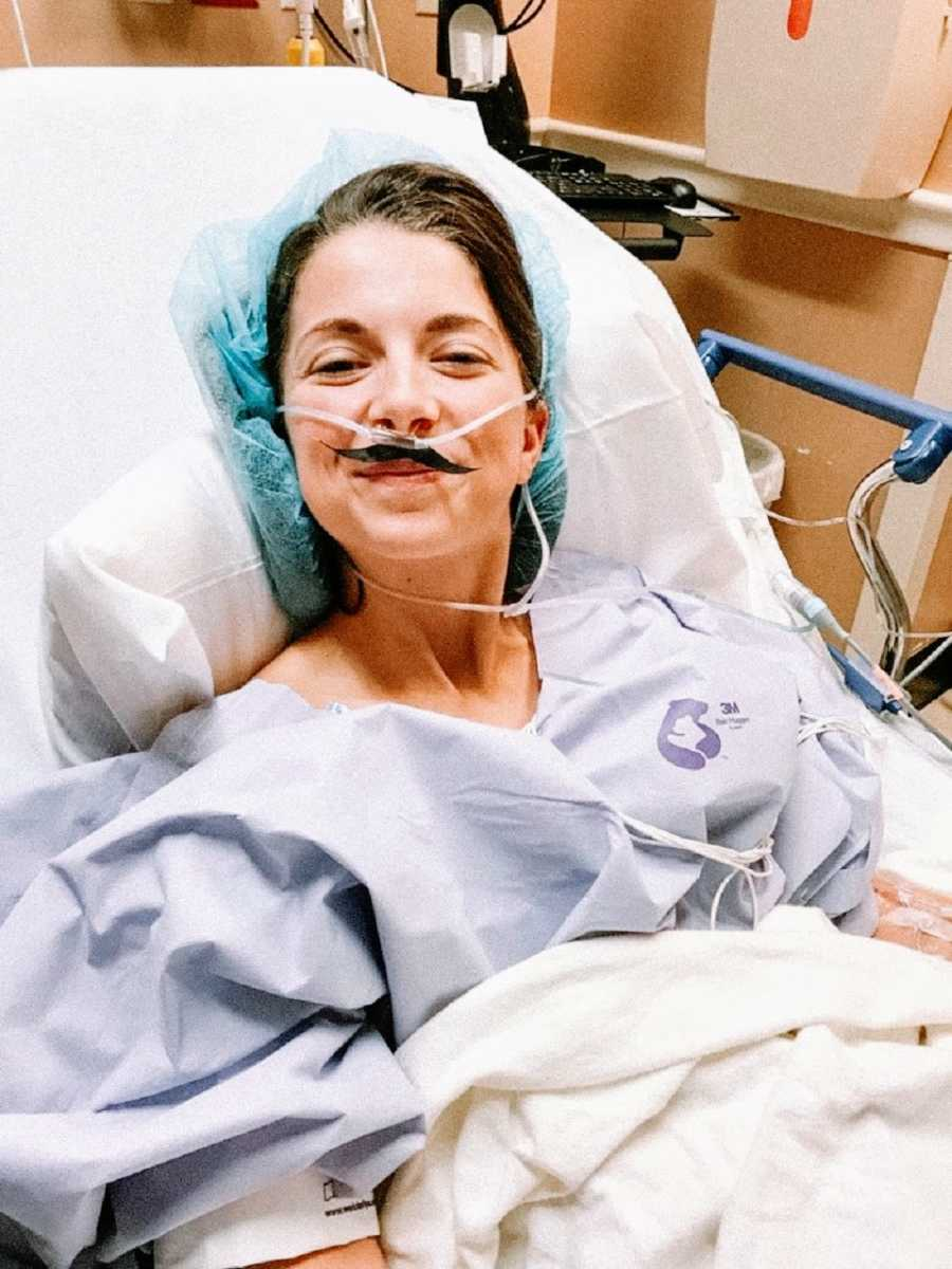 Spinal tumor survivor wears tubes and paper moustache