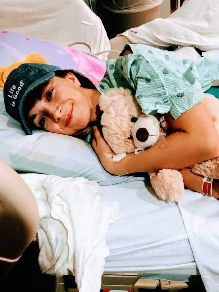 Chronically ill woman lying in hospital bed with teddy bear