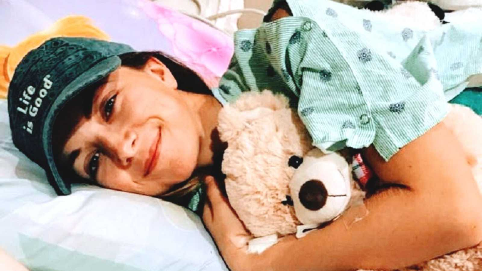 Chronic illness patient lies in hospital bed with stuffed bear
