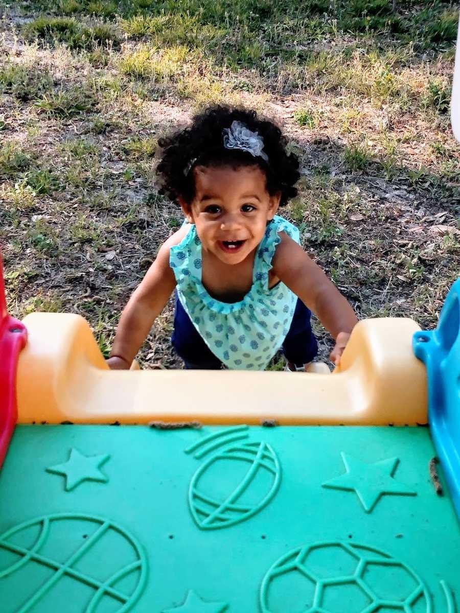 A little girl climbs up a plastic play slide