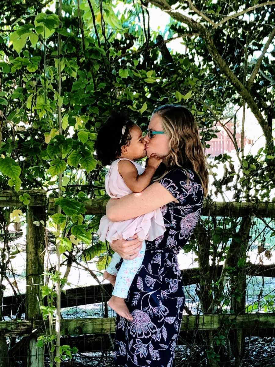 A mother gives her baby girl a kiss on the lips