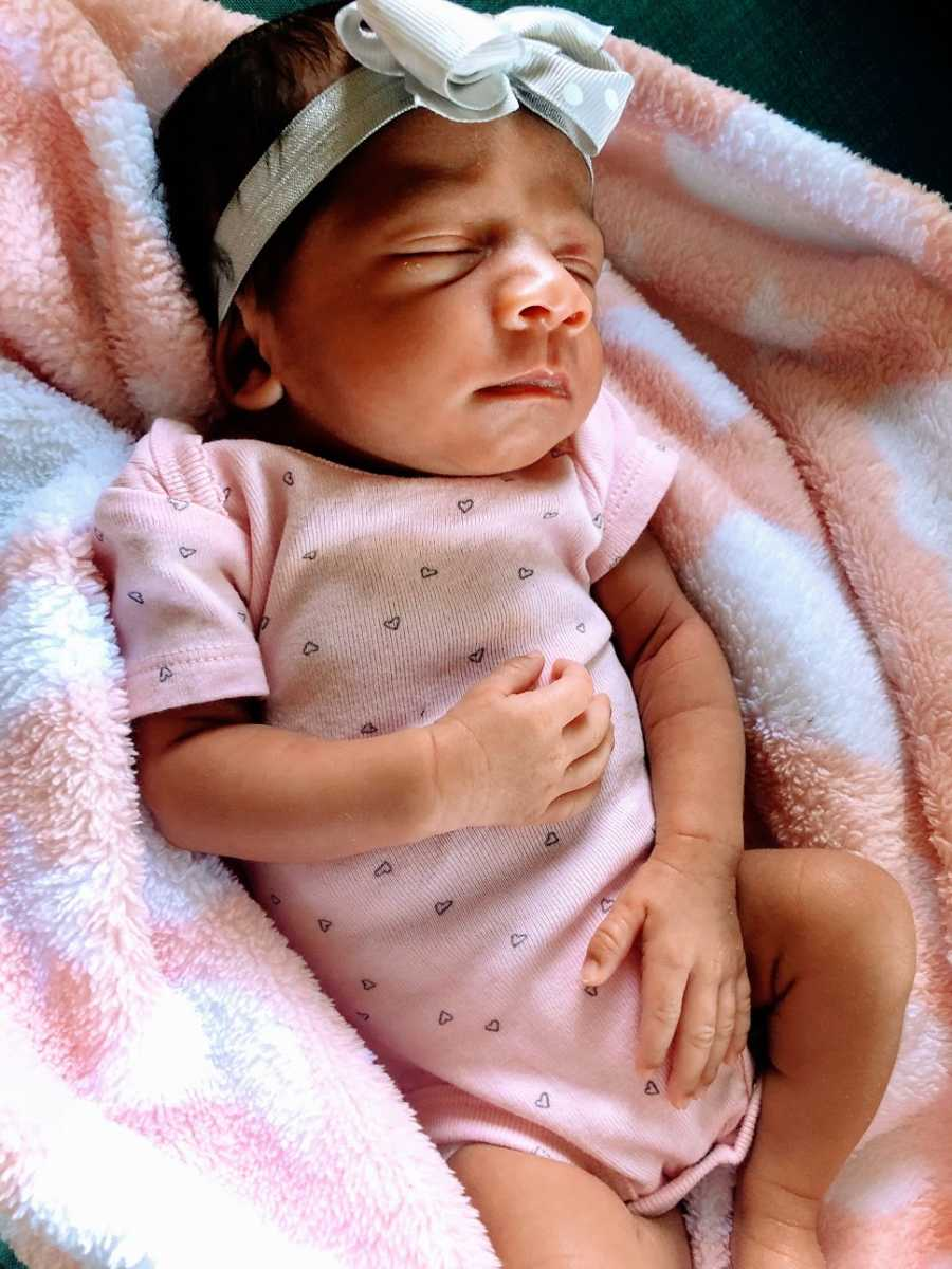 A baby girl wearing a pink shirt lies on a blanket