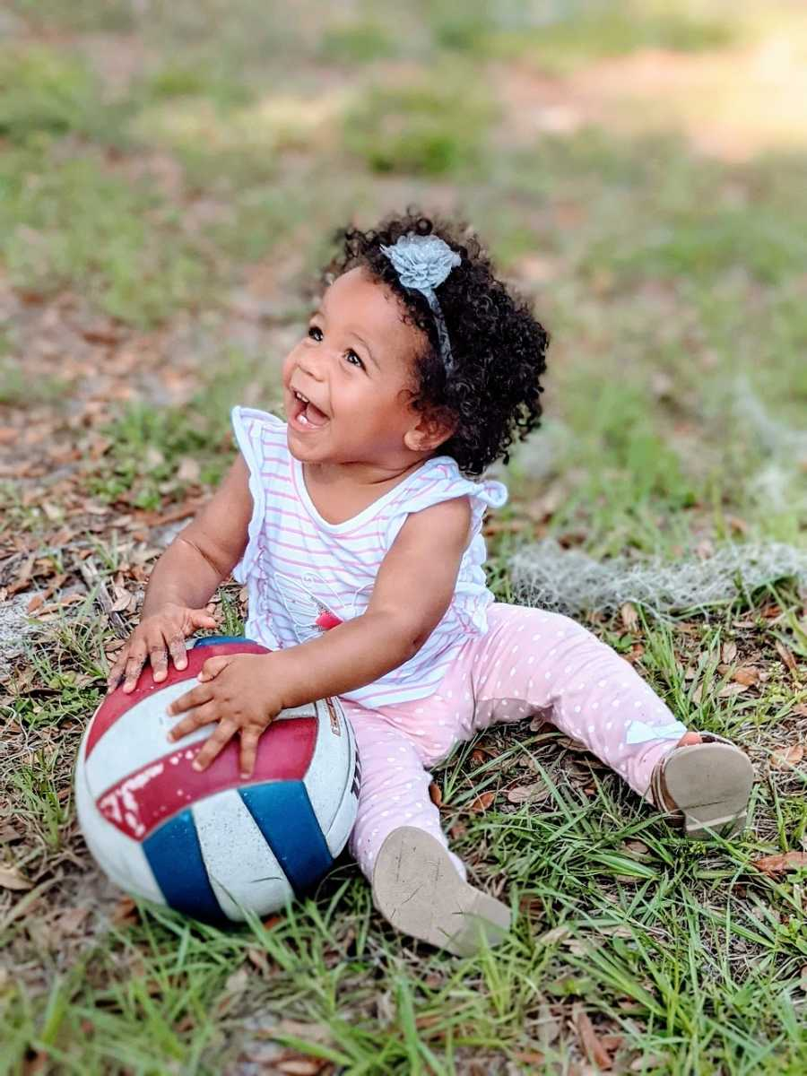 A little girl plays with a volleyball