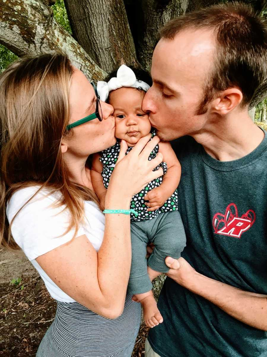 Parents kiss their baby girl on either cheek