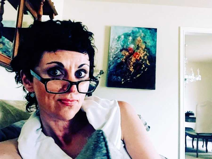 A woman sits with glasses askew on her nose
