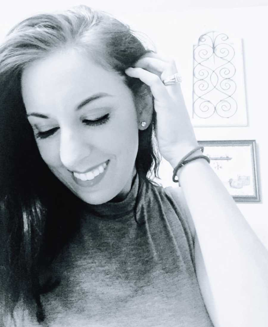 A woman turns her head to the side and smiles with one hand in her hair