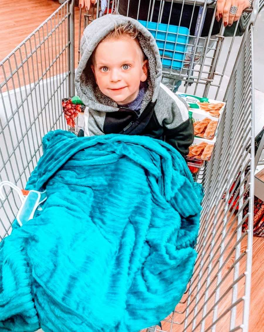 A little boy sits in a blanket in a shopping cart