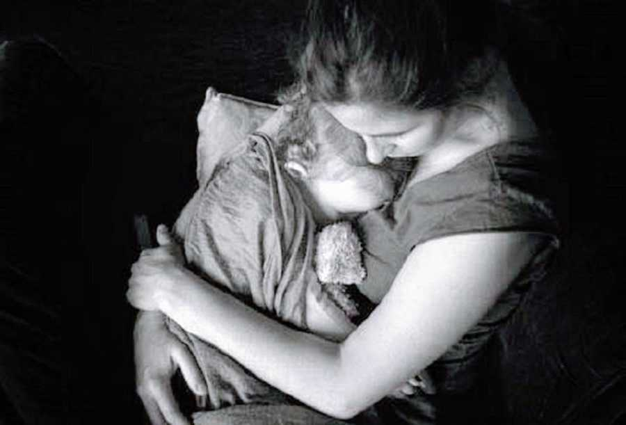 A mother cuddles with her sleeping son