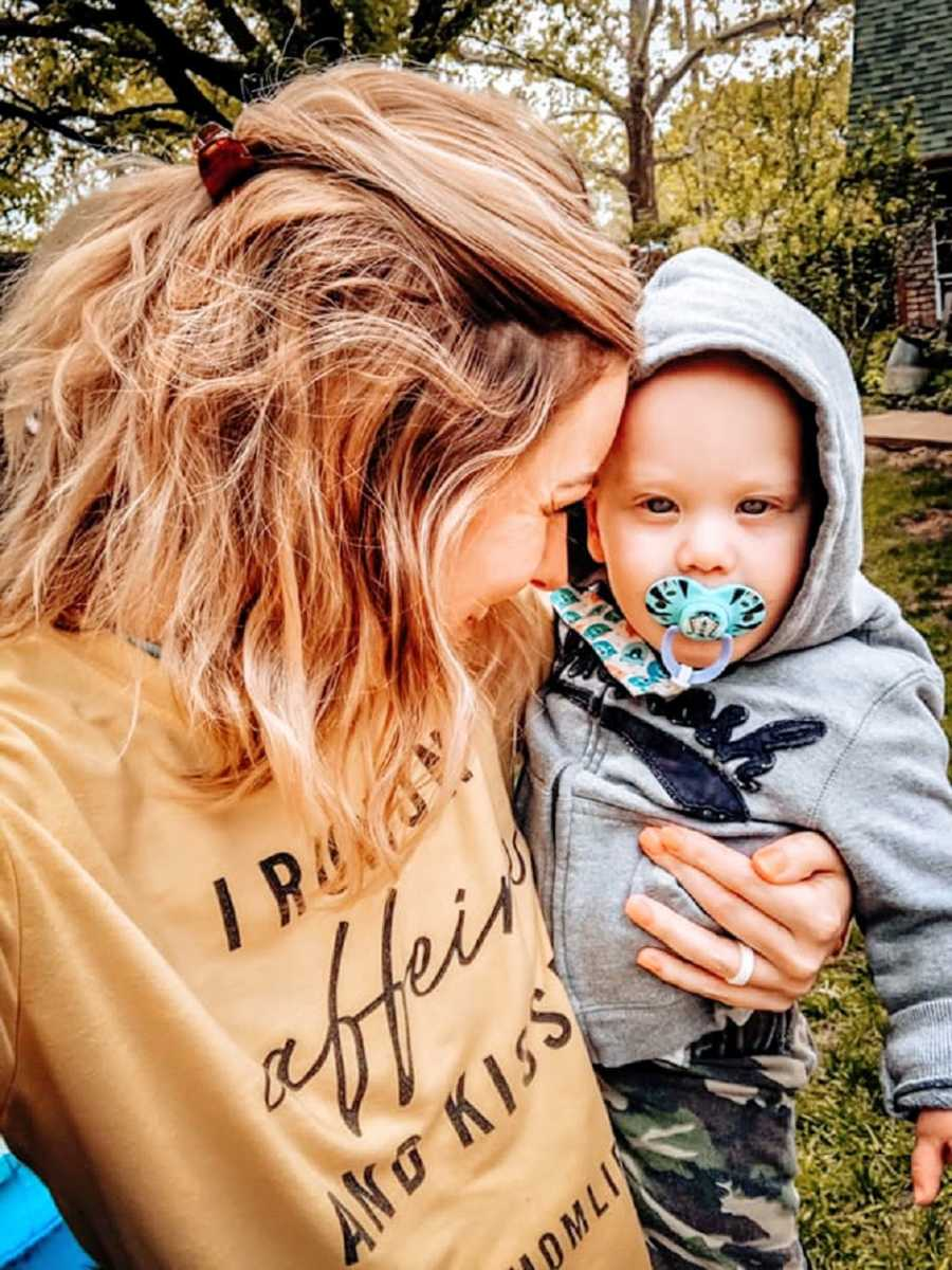 A mother holds her toddler, who has a pacifier in his mouth